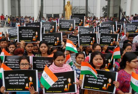"""Students hold placards during a vigil to pay tribute to Central Reserve Police Force (CRPF) personnel who were killed after a suicide bomber rammed a car into a bus in south Kashmir on Thursday, in Agartala, India February 16, 2019. The placards read """"Tribute to brave sons of mother India martyred in Kashmir"""". REUTERS/Jayanta Dey"""