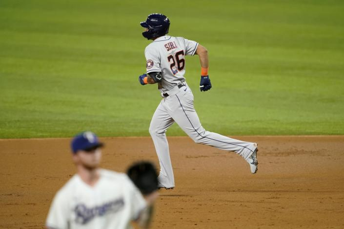 Houston Astros' Jose Siri rounds the bases after hitting a two-run home run off of Texas Rangers starting pitcher A.J. Alexy, front, in the third inning of a baseball game in Arlington, Texas, Monday, Sept. 13, 2021. The shot scored Jake Meyers. (AP Photo/Tony Gutierrez)
