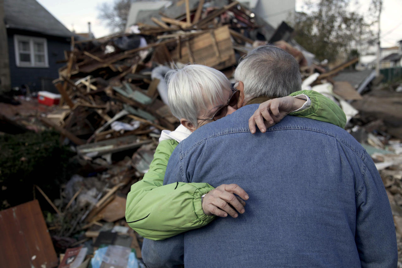 <p>               Sheila and Dominic Traina hug in front of their home which was demolished during Superstorm Sandy in Staten Island, N.Y., Friday, Nov. 2, 2012.  Mayor Michael Bloomberg has come under fire for pressing ahead with the New York City Marathon. Some New Yorkers say holding the 26.2-mile race would be insensitive and divert police and other important resources when many are still suffering from Superstorm Sandy. The course runs from the Verrazano-Narrows Bridge on hard-hit Staten Island to Central Park, sending runners through all five boroughs. The course will not be changed, since there was little damage along the route.  (AP Photo/Seth Wenig)