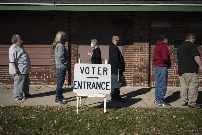 "In this Nov. 3, 2020, photo, voters wait in line outside a polling center on Election Day, in Kenosha, Wis. President-elect Joe Biden shored up the Democrats' ""blue wall,"" — more sturdily in Michigan, more tenuously in Pennsylvania and Wisconsin — to rebuild the party's path back to the White House. (AP Photo/Wong Maye-E, File)"