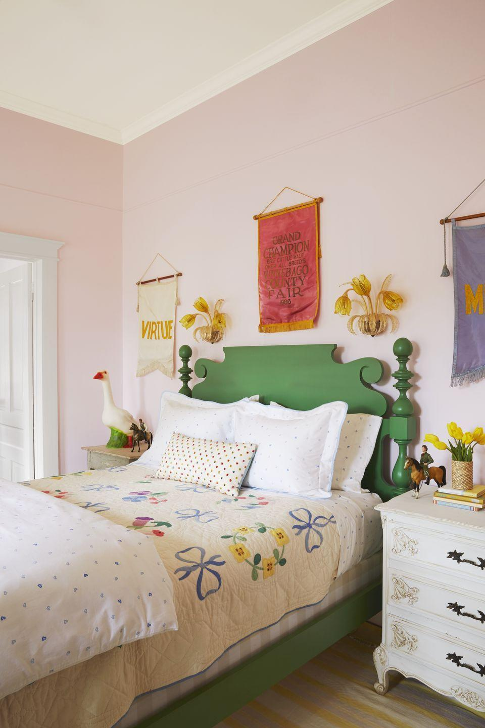 """<p><a href=""""https://www.biscuit-home.com/"""" rel=""""nofollow noopener"""" target=""""_blank"""" data-ylk=""""slk:Designer Bailey McCarthy"""" class=""""link rapid-noclick-resp"""">Designer Bailey McCarthy</a> embraced her love of pink and green full tilt by painting the walls in her daughter's room a soft shade of the former and choosing a traditional country bed frame in a leafy shade of the latter. An antique quilt looks surprisingly modern when paired with <a href=""""https://www.biscuit-home.com/products/grace-duvet-pale-blue-blue"""" rel=""""nofollow noopener"""" target=""""_blank"""" data-ylk=""""slk:graphic heart print bedding"""" class=""""link rapid-noclick-resp"""">graphic heart print bedding</a> from her Biscuit Home line. Vintage finds, like the Murano glass tulip wall sconces and the silk county fair banners hanging above the bed, infuse the grown-up-worthy child's bedroom with personality.</p><p><strong>Get the Look: </strong><br>Wall Paint Color: <a href=""""https://go.redirectingat.com?id=74968X1596630&url=https%3A%2F%2Fwww.farrow-ball.com%2Fen-us%2Fpaint-colours%2Fmiddleton-pink&sref=https%3A%2F%2Fwww.countryliving.com%2Fremodeling-renovation%2Fhome-makeovers%2Fg32468539%2Fbest-bedroom-paint-colors-ideas%2F"""" rel=""""nofollow noopener"""" target=""""_blank"""" data-ylk=""""slk:Middleton Pink by Farrow & Ball"""" class=""""link rapid-noclick-resp"""">Middleton Pink by Farrow & Ball</a></p>"""