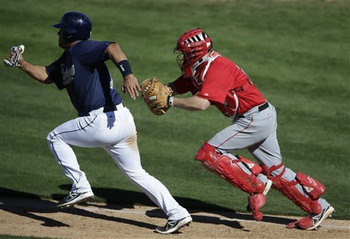 Los Angeles Angels catcher Luke Carlin, right, chases down and tags out San Diego Padres' Eddy Rodriguez during the ninth inning in an exhibition spring training baseball game on Wednesday, March 13, 2013, in Peoria, Ariz. (AP Photo/Gregory Bull)