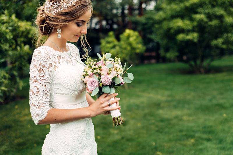 the bride in a white long dress with a wedding bouquet is standing alone and looks at a bouquet waiting for her husband in the autumn garden. after wedding ceremony