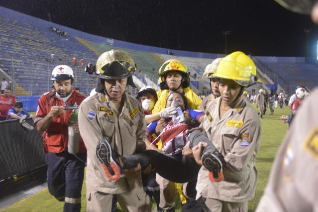 Firefighters carry away a fan hit by tear gas fired by police to break up deadly fights between fans before a game between Motagua and Olimpia in Tegucigalpa, Honduras, on Saturday. (Victor Colindres/La Tribunal via AP)