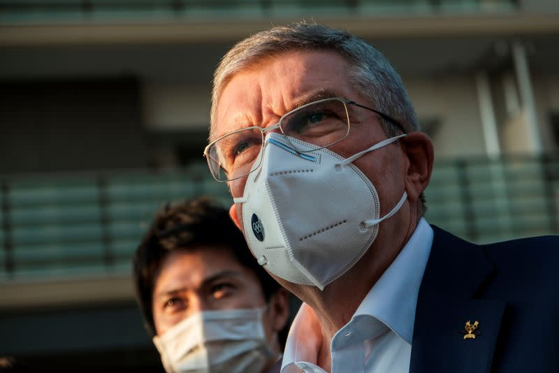 Thomas Bach, International Olympic Committee (IOC) President wearing a protective mask talks to journalists during a visit to Olympic and Paralympic village in Tokyo
