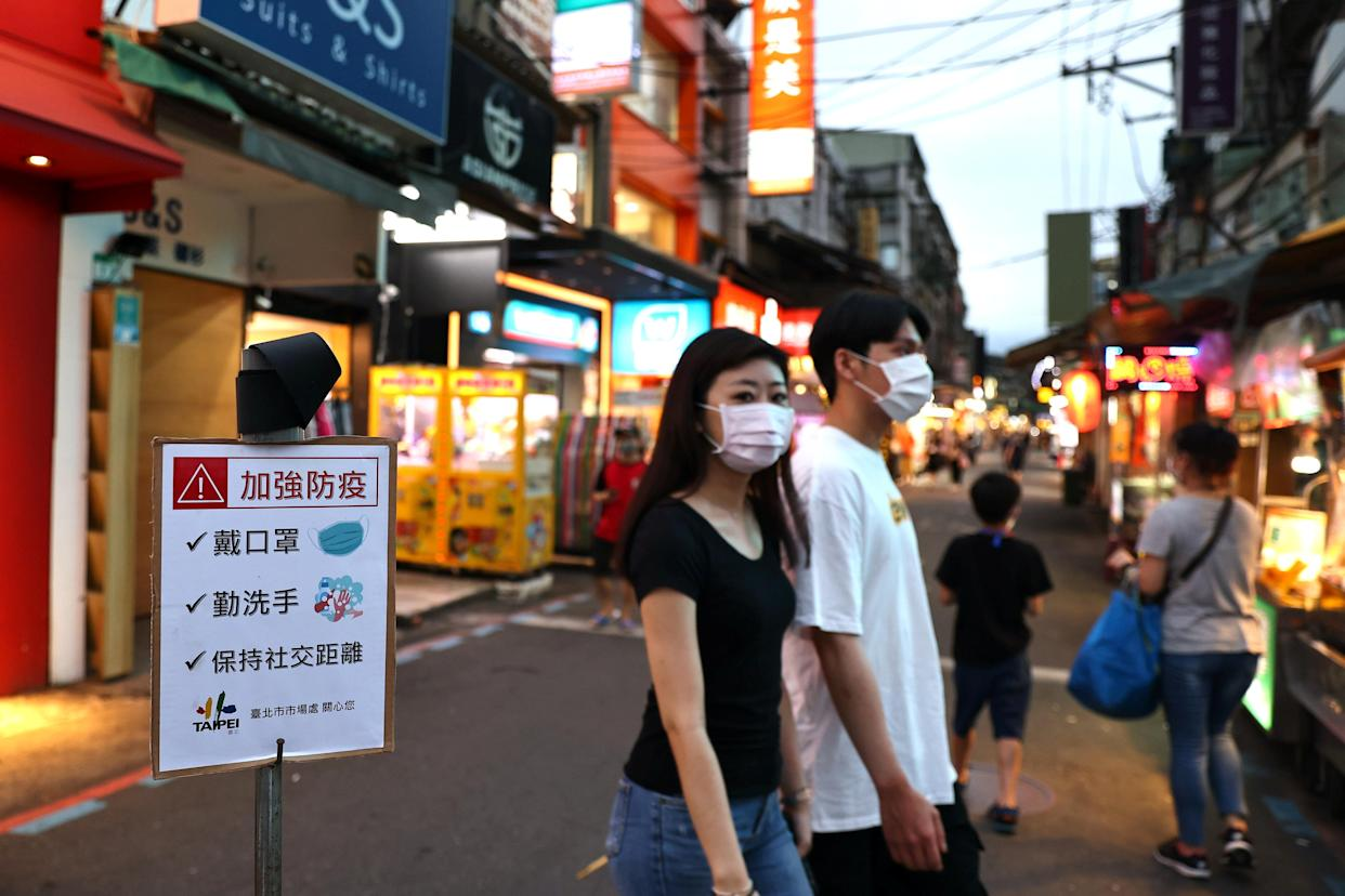 People wearing protective face masks walk past a sign reading