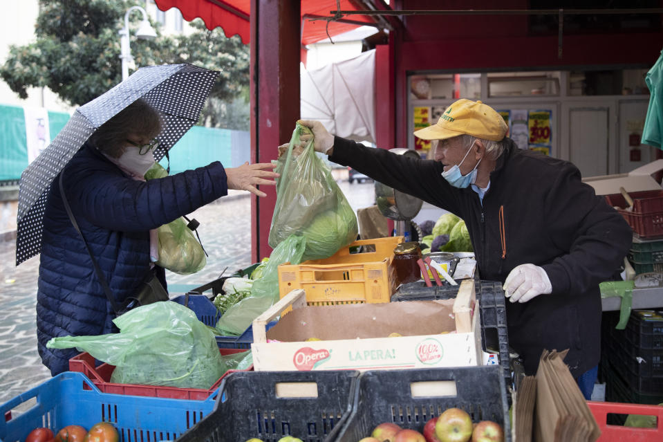 Domenico Zoccoli, 80, serves a client in the open air market where he works, in Rome, Wednesday, Dec. 2, 2020. In Italy, which has the world's second-oldest population, many people in their 70s and older have kept working through the COVID-19 pandemic. From neighborhood newsstand dealers to farmers bring crops to market, they are defying stereotypic labels that depict the old as a monolithic category that's fragile and in need of protection. (AP Photo/Alessandra Tarantino)