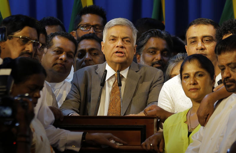Sri Lanka's reinstated prime minister Ranil Wickeremesinghe, center, surrounded by his loyal lawmakers and supporters speaks after assuming duties in Colombo, Sri Lanka, Sunday, Dec. 16, 2018. Sri Lanka's president has reappointed Ranil Wickremesinghe as prime minister, nearly two months after firing him and setting off weeks of political stalemate. (AP Photo/Eranga Jayawardena)