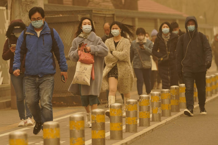 Residents make their way through a sandstorm in Beijing, Monday, March 15, 2021. The sandstorm brought a tinted haze to Beijing's skies and sent air quality indices soaring on Monday. (AP Photo/Ng Han Guan)