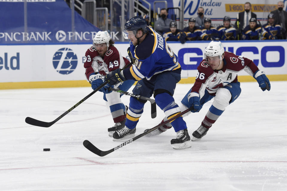 Colorado Avalanche's Samuel Girard (49), left and Mikko Rantanen (96) defend against St. Louis Blues' Vladimir Tarasenko (91) during the second period of an NHL hockey game on Wednesday, April 14, 2021, in St. Louis. (AP Photo/Joe Puetz)