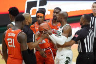 Referees separate Illinois guard Trent Frazier, center, and Michigan State guard Joshua Langford during the second half of an NCAA college basketball game, Tuesday, Feb. 23, 2021, in East Lansing, Mich. (AP Photo/Carlos Osorio)