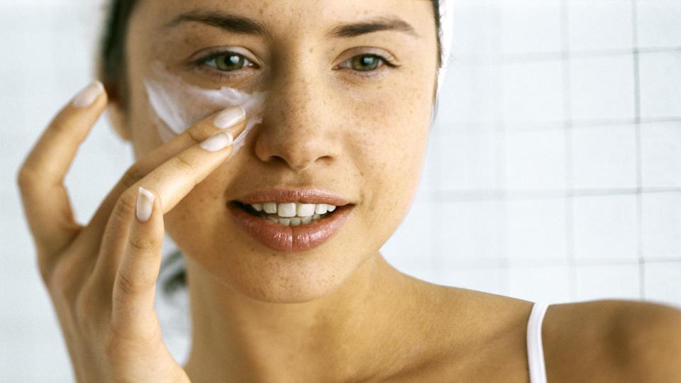 Woman applying moisturizer beneath eye