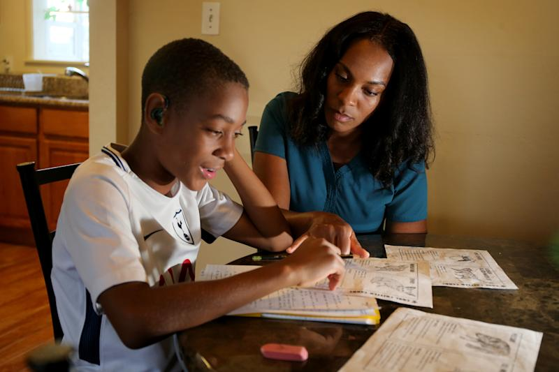RICHMOND, CA - SEPTEMBER 11: Jasmine Porter helps her son Dontae Butler, 11, with his homework at the apartment where they live in Richmond, Calif., on Tuesday, Sept. 11, 2018. According to local realtors, homes aren't selling for as much as they did several months ago and are taking longer to sell. Porter is looking to buy a house. (Ray Chavez/Digital First Media/The Mercury News via Getty Images)