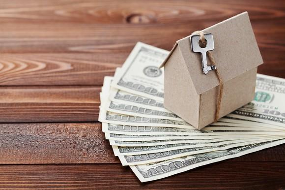 Cardboard house sitting on $100 bills