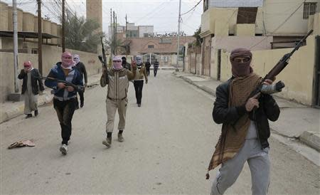 Gunmen fighters walk in the streets of the city of Ramadi December 30, 2013. REUTERS/Ali al-Mashhadani