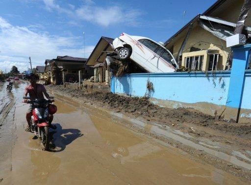 A car hangs on a wall of a house, which was swept away at the height of the devastating floods in Iligan City on the southern island of Mindanao. The death toll from a destructive storm that hit the southern Philippines has risen to 927 as bodies surfaced in the sea, the head of the government disaster monitoring council said Tuesday