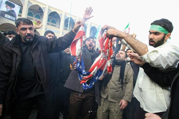 """Iranians burn a US flag during a demonstration against American """"crimes"""" in Tehran following the killing of Iranian Revolutionary Guards Major General Qasem Soleimani in a US strike on his convoy at Baghdad international airport (AFP Photo/ATTA KENARE)"""