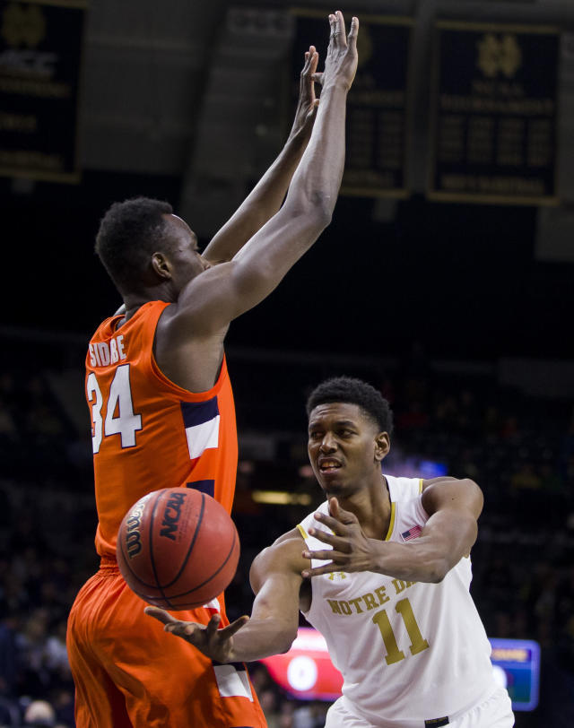 Notre Dame's Juwan Durham (11) passes the ball around Syracuse's Bourama Sidibe(34) during the first half of an NCAA college basketball game Wednesday, Jan. 22, 2020, in South Bend, Ind. (AP Photo/Robert Franklin)