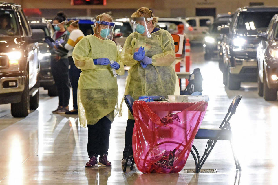 FILE - In this Sept. 8, 2020, file photo, Bismarck-Burleigh Public Health nurses Crys Kuntz, left, and Sara Nelson confer inside the Bismarck Event Center in Bismarck, N.D., where vehicles were lined up for the weekly drive-thru COVID-19 testing. A surge of coronavirus cases in Wisconsin and the Dakotas is forcing a scramble for hospital beds and raising political tensions, as the Upper Midwest and Plains emerge as one of the nation's most troubling hotspots. (Tom Stromme/The Bismarck Tribune via AP, File)