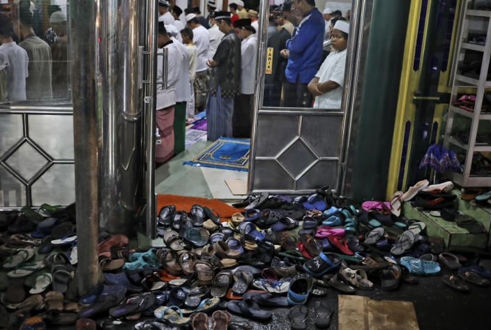 Footwear are left outside as people perform perform an evening prayer called 'tarawih' during the first evening of the holy fasting month of Ramadan, at a mosque in Jakarta, Indonesia, Monday, April 12, 2021. (AP Photo/Dita Alangkara)
