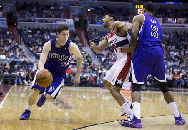 Sacramento Kings small forward Rudy Gay, right, sets a pick against Washington Wizards shooting guard Garrett Temple for teammate Jimmer Fredette during the first half of an NBA basketball game, Sunday, Feb. 9, 2014, in Washington. (AP Photo/ Evan Vucci)