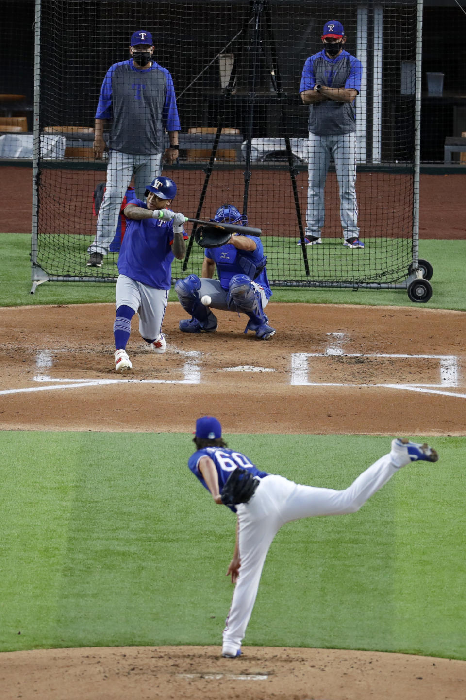 Texas Rangers' Luke Farrell throws to Willie Calhoun as catcher Jeff Mathis, pitching coach Julio Rangel, left rear and manager Chris Woodward, right rear, look on during a baseball practice at Globe Life Field in Arlington, Texas, Friday, July 3, 2020. (AP Photo/Tony Gutierrez)