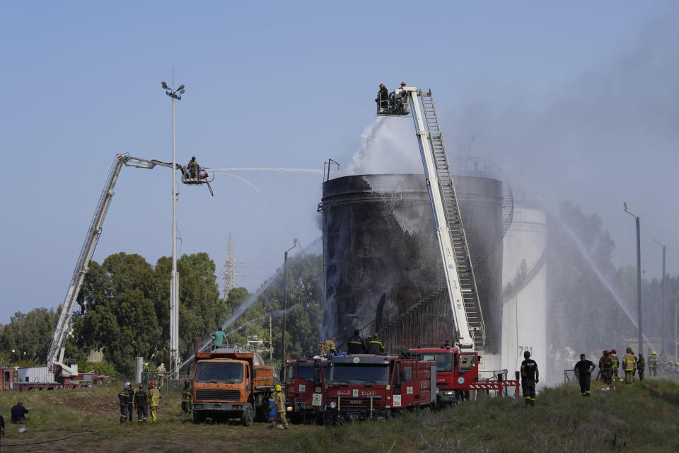Firefighters work to extinguish a fire at an oil facility in the southern town of Zahrani, south of the port city of Sidon, Lebanon, Monday, Oct. 11, 2021. The cause of the fire was not immediately known. (AP Photo/Hassan Ammar)