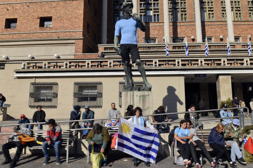 Fans of Uruguay's national soccer team mill around a replica of Michelangelo's David wearing a team jersey, outside the Montevideo City hall, before a television broadcast of the Russia 2018 World Cup match between Saudi Arabia and Uruguay in Montevideo, Uruguay, Wednesday, June 20, 2018. (AP Photo/Matilde Campodonico)