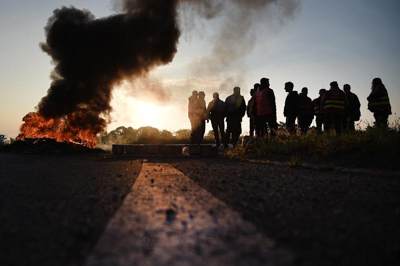 Workers on strike stand next to burning barricade outside the Total refinery in Donges, on May 17, 2016 (AFP Photo/Jean-Sebastien Evrard)