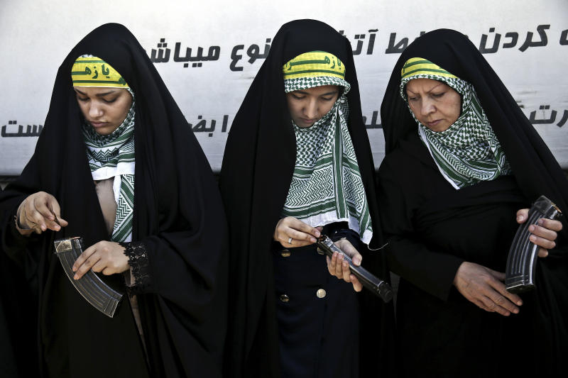 In this Thursday, Aug. 22, 2013 photo, female members of the Basij paramilitary militia load their rifles during a training session in Tehran, Iran. With a presence in nearly every city and town across Iran, the paramilitary Basij volunteer corps has an ever-increasing influence on life in the Islamic Republic. (AP Photo/Ebrahim Noroozi)