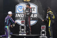 Will Power, center, of Australia, Romain Grosjean, left, of Switzerland, and Colton Herta celebrate on the victory podium following an IndyCar auto race at Indianapolis Motor Speedway, Saturday, Aug. 14, 2021, in Indianapolis. Power won the race, Grosjean finished second and Herta finished third. (AP Photo/Darron Cummings)