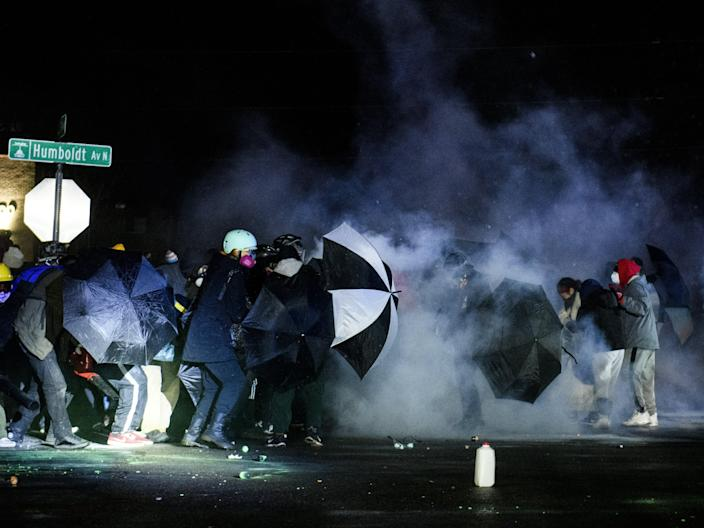 <p>Protesters confront law enforcement outside the Brooklyn Center police headquarters on 13 April, 2021 in Brooklyn Center, Minnesota</p> (Getty Images)
