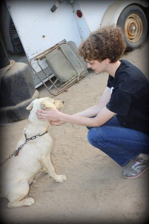 woman with short curly hair petting a dog