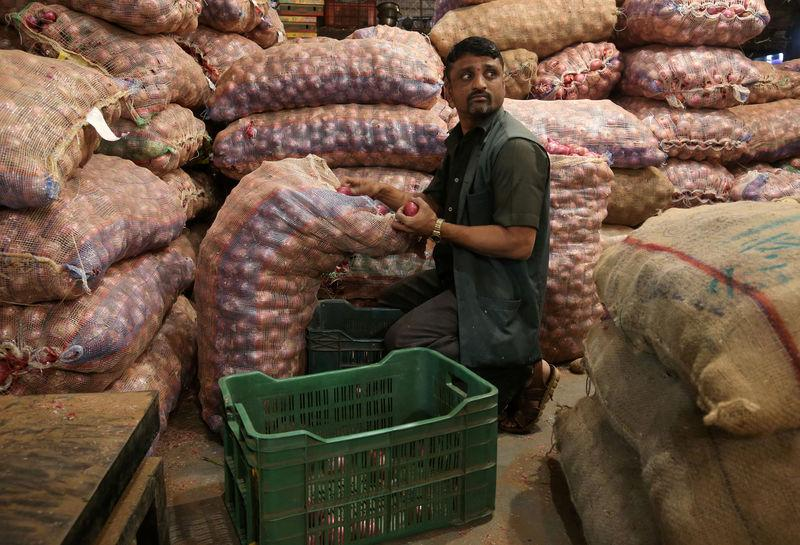 A man sorts onions at a vegetable wholesale market in Mumbai