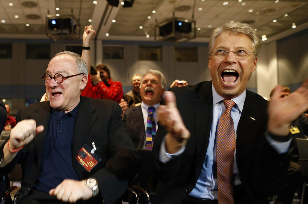 European Space Agency (ESA) Director General Jean-Jacques Dordain (L) and European Space Operations Centre (ESOC) Director General Thomas Reiter react after ESA's satellite Rosetta resent a signal to ESOC in Darmstadt January 20, 2014. Comet-chasing spacecraft Rosetta woke from nearly three years of hibernation on Monday to complete a decade-long deep space mission that scientists hope will help unlock some of the secrets of the solar system. Rosetta, which was launched by the ESA in 2004, is due to rendezvous with comet 67P/Churyumov-Gerasimenko and land a probe on it this year in an unprecedented manoeuvre. REUTERS/Ralph Orlowski (GERMANY - Tags: SCIENCE TECHNOLOGY)