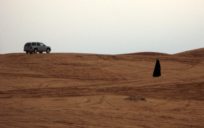 FILE - In thos Friday, Nov. 7, 2008 file photo, a Saudi woman walks in the desert, in Thumama, Saudi Arabia. It's been a little more than two years since the last time women in Saudi Arabia campaigned for the right to drive. Since then, the monarchy has made incremental but key reforms, and activists hope that has readied the nation for greater change as they call for women to get behind the wheel in a new campaign Saturday, Oct. 26, 2013. Ultraconservatives are pushing back with protests, threats and even a cleric's warning that driving a car damages a woman's ovaries. (AP Photo/Hassan Ammar, File)