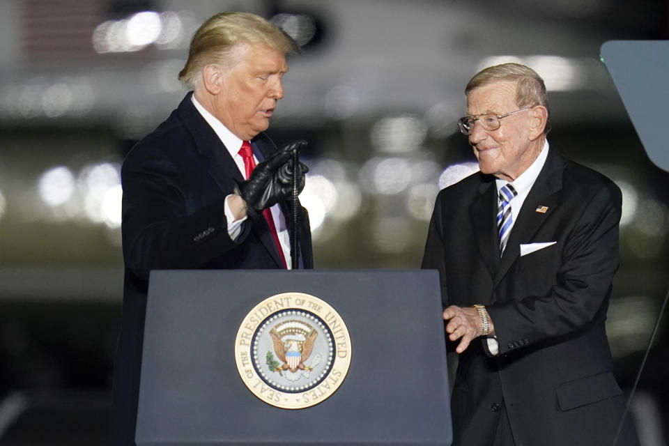 President Donald Trump, left, introduces former college football coach Lou Holtz during a campaign stop, Saturday, Oct. 31, 2020, at the Butler County Regional Airport in Butler, Pa. (AP Photo/Keith Srakocic)