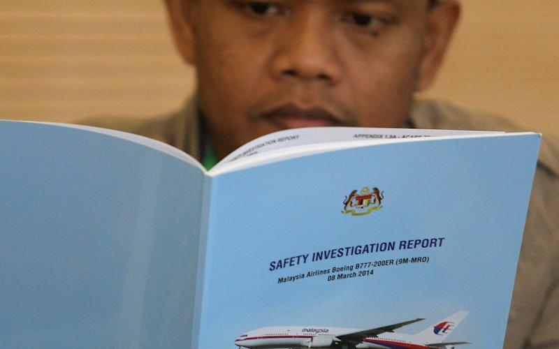 A family member reads an MH370 briefing report before a closed door meeting in Putrajaya - REUTERS
