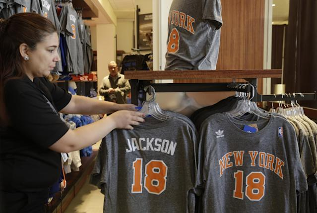A New York Knicks store employee arranges Phil Jackson t-shirts prior to a news conference where he was introduced as the new president of the New York Knicks, Tuesday, March 18, 2014 in New York. Jackson, who won two NBA titles as a player with the Knicks, also won 11 championships while coaching the Chicago Bulls and the Los Angeles Lakers. (AP Photo/Mark Lennihan)