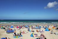 Porthmeor Beach on a brillantly clear August day, just one little white cloud. People sun bathing and swimming.