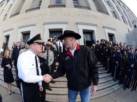 New Interior Secretary Ryan Zinke (R) greets employees after riding in on horseback with a U.S. Park Police horse mounted unit to report for his first day of work at the Interior Department in Washington, U.S., March 2, 2017.  Tami Heilemann/Department of Interior/Handout via REUTERS