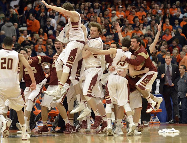 Boston College players celebrate after defeating Syracuse 62-59 in overtime in an NCAA college basketball game in Syracuse, N.Y., Wednesday, Feb. 19, 2014. (AP Photo/Kevin Rivoli)