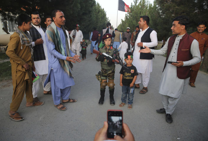 A man takes a picture of his son with an Afghan boy dressed as soldier during Independence Day celebrations in Kabul, Afghanistan, Monday, Aug. 19, 2019. Afghanistan's president is vowing to eliminate all safe havens of the Islamic State group as the country marks a subdued 100th Independence Day after a horrific wedding attack claimed by the local IS affiliate. (AP Photo/Rafiq Maqbool)