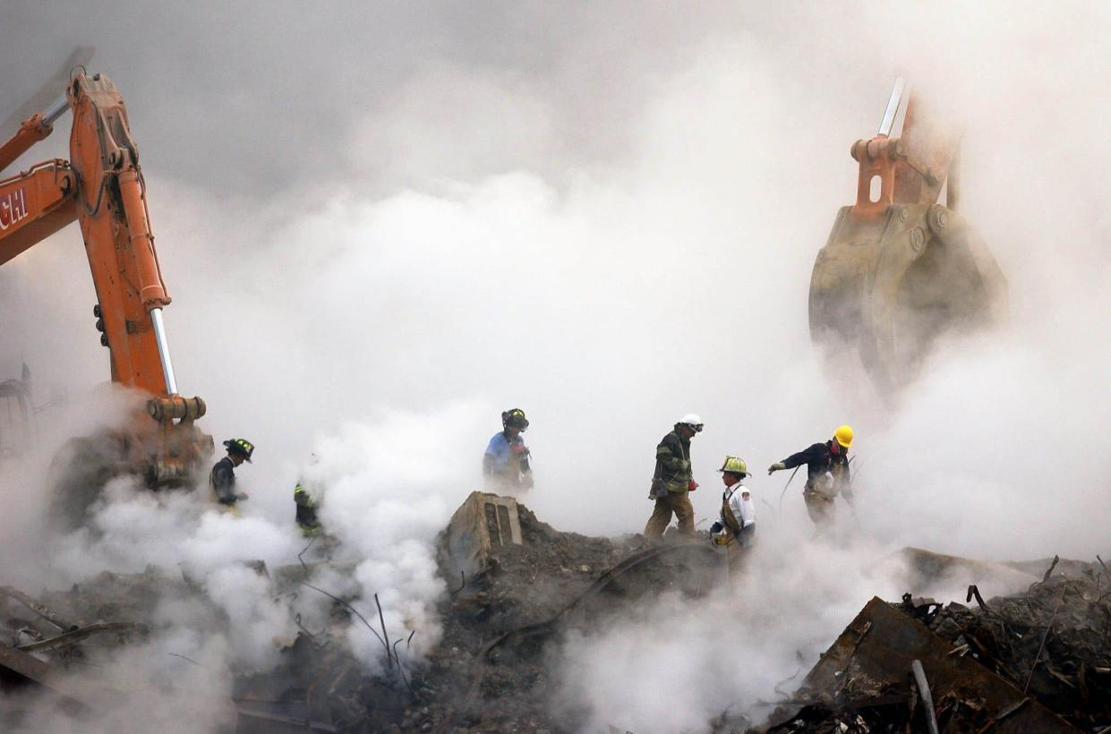 In this Oct. 11, 2001 file photo, firefighters make their way over the ruins of the World Trade Center through clouds of dust and smoke at ground zero in New York.