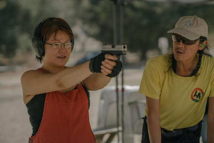 AZUSA, CALIFORNIA - JULY 18, 2021:Svetlana Kim practices shooting her handgun, while standing next to Tom Nguyen, instructor and founder of L.A. Progressive Shooters, at Burro Canyon Shooting Park in Azusa, CA. Svetlana attended beginner's classes through L.A. Progressive Shooters. Tom founded L.A. Progressive Shooters in the hopes of diversifying the population of gun owners and making gun ownership more inclusive of minorities. Isadora Kosofsky for TIME