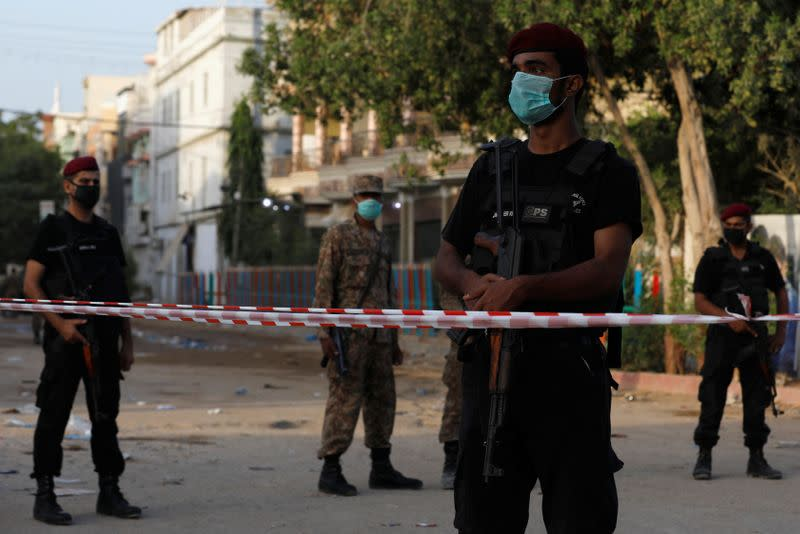 Police officers guard a cordoned-off street leading to the site of a passenger plane crash in a residential area near an airport in Karachi,