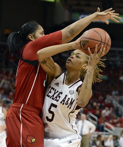 CORRECTS DATE - Texas A&M's Kristi Bellock, left, tries to get a shot off past the defense of Louisville's Monique Reid during the first half of an NCAA women's college basketball game Friday, Nov. 9, 2012, in Louisville, Ky. (AP Photo/Timothy D. Easley)