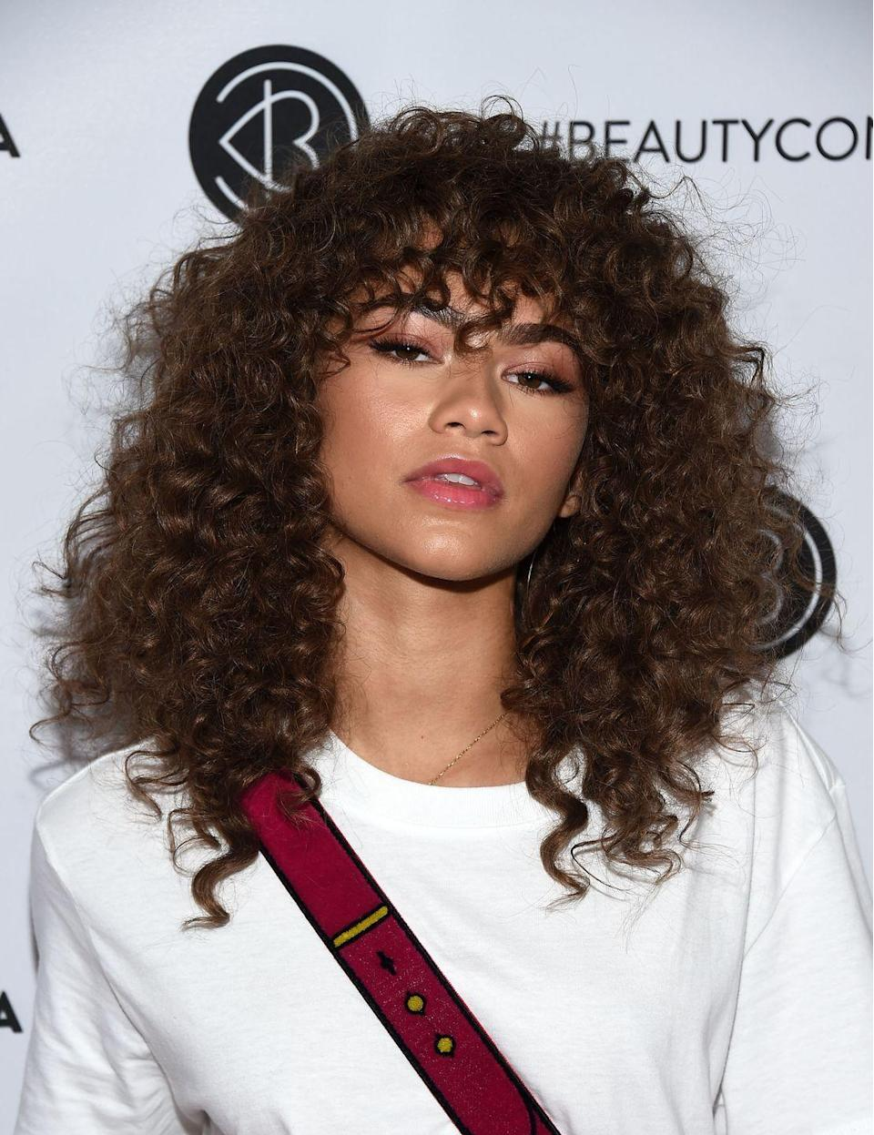 "<p>Whether your hair is super long or medium length like actress Zendaya's, these <a href=""https://www.goodhousekeeping.com/beauty/hair/g33267765/types-of-bangs/"" rel=""nofollow noopener"" target=""_blank"" data-ylk=""slk:curly bangs"" class=""link rapid-noclick-resp"">curly bangs</a> channel instant cool.</p>"