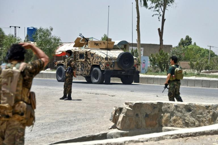 Afghan security personnel stand guard along a road in Kandahar during fighting between Afghan security forces and Taliban fighters