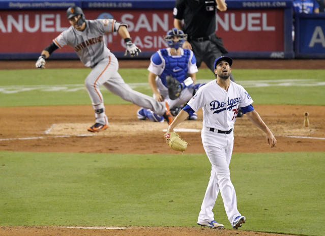 San Francisco Giants' Chase d'Arnaud, left, hits a single as Los Angeles Dodgers relief pitcher Scott Alexander, right, watches along with catcher Austin Barnes during the ninth inning of a baseball game, Monday, Aug. 13, 2018, in Los Angeles. (AP Photo/Mark J. Terrill)